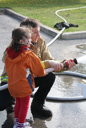 Little girl being shown how a fire hose works