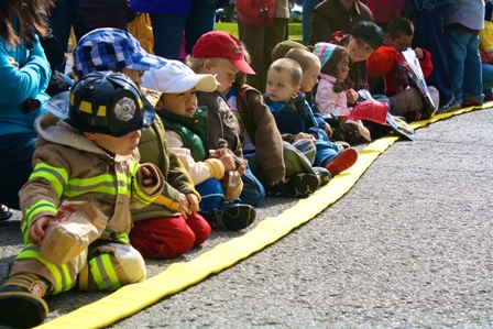 Kids lined up by a fire hose
