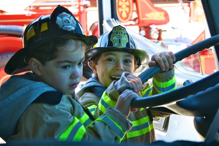 Little kids dressed up as fire fighters,